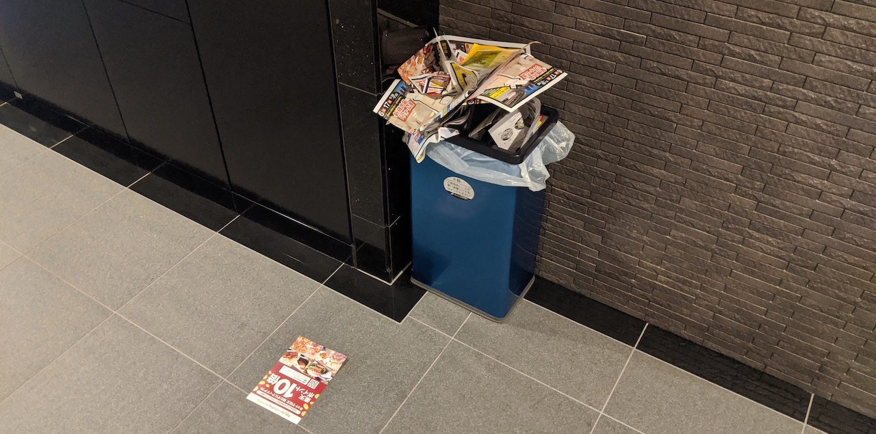 Rubbish bin near mailbox overflowing with junk mail received by residents